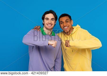 Hugging Interracial Hipsters Smiling With Fist Bump Gesture Isolated On Blue.