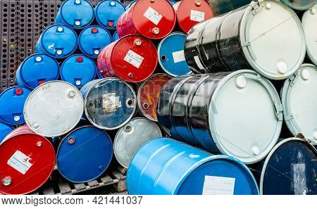 Old Chemical Barrels On Wooden Pallet. Blue And Red Oil Drum. Steel And Plastic Oil Tank. Toxic Wast