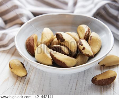 Bowl With Brazil Nuts On Wooden Table