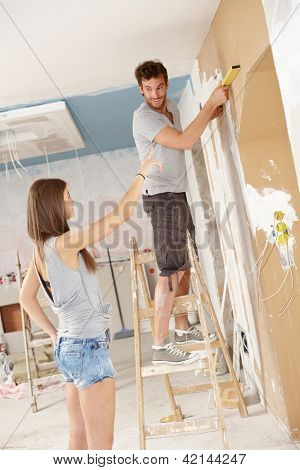 Young couple renovating home, DIY, measuring.