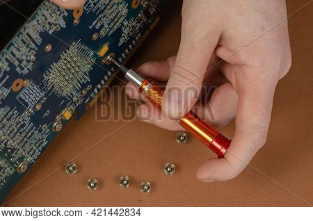Graphics Card On A Brown Background. Man Disassembles Computer Components, Unscrewing Screws. Repair