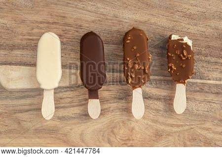 Stick Ice Cream On A Wooden  Background. Vanilla Eskimo Ice-cream Bar. Popsicle And Lolly Sweet Dess