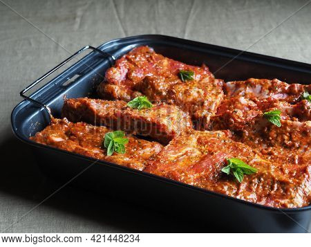 Marinated Meat On A Baking Tray Ready For Baking In The Oven. Fresh Raw Lamb Loin Spare Ribs With Sp