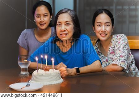 Elderly Mother And Two Adult Daughter Are Celebrating A Birthday With Birthday Cake