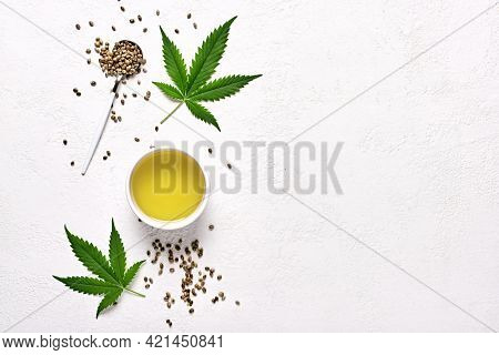 Hemp Oil In Bowl, Leaves And Seeds On White Background, Flat Lay With Copy Space
