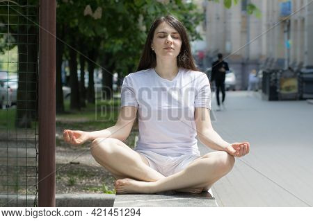 A Woman Meditates On The Street In The City. Meditation And Yoga