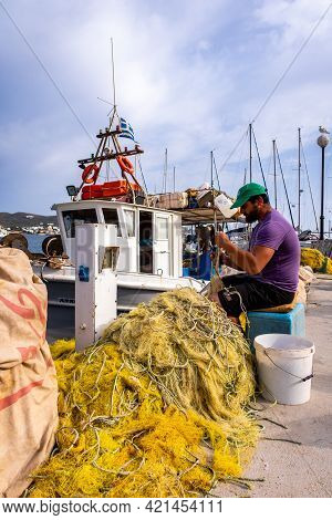 Finikas, Siros, Greece, 27.05.2019. Greek Fisherman Repairing His Nylon Fishing Nets On The Pier In