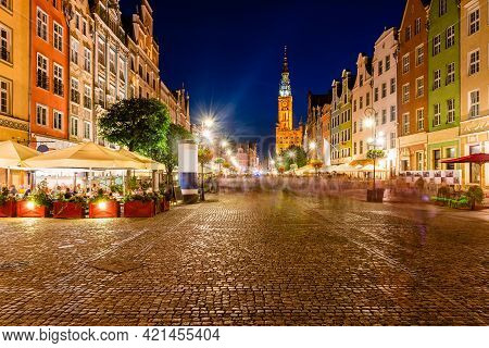 Old Town Of Gdansk, Night View On Street Cafe And Walking People, Photo Made With Long Exposure