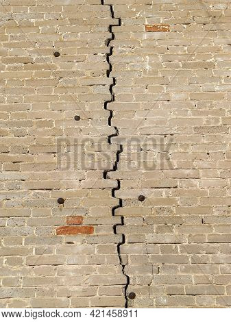Texture Of An Old Weathered Brick Wall With Big Crack In The Middle Fastened With Rusty Cut Masonry
