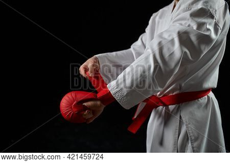 Male karate fighter having red belt and gloves