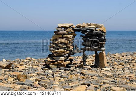Intricately Stacked Flat Stones In A Pyramid On The Seashore. Vacation By The Sea. Selective Focus.