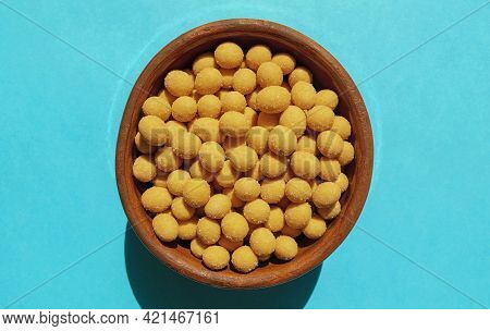 Cheese Coated Salted Peanuts In A Brown Bowl On Bluea Background. Fried Peanut Grains With A Coating