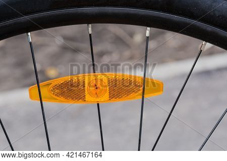 Fragment Of Bicycle Wheel With Plastic Reflector Orange Color Installed Between The Spokes