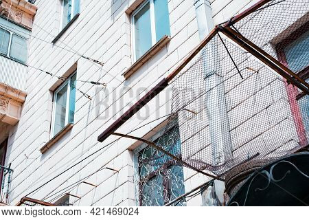 Iron Rusty Grid Wire Installed On A Facade Of The Building To Protect Pedestrian From The Falling Pa