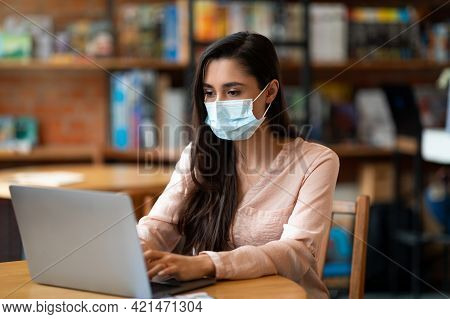 New Normal And Distant Work. Arab Woman In Mask Typing On Laptop Computer, Working Distantly From Ca