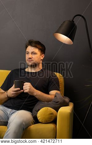 Unshaven Bored Man With Cup Of Coffee Looking Away Sitting On Comfy Yellow Sofa