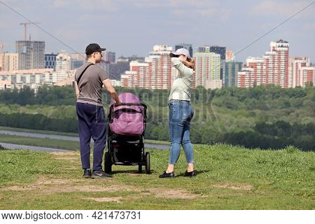 Moscow, Russia - May 2021: Couple With Baby Pram Standing On Top Of A Hill On Background Of City And