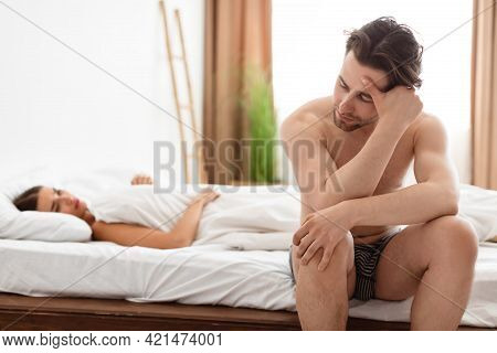 Unhappy Man Having Erection Problems While Girlfriend Lying In Bedroom