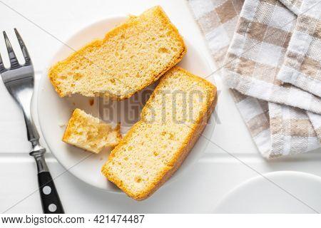Sliced sponge dessert. Sweet sponge cake on white kitchen table. Top view.