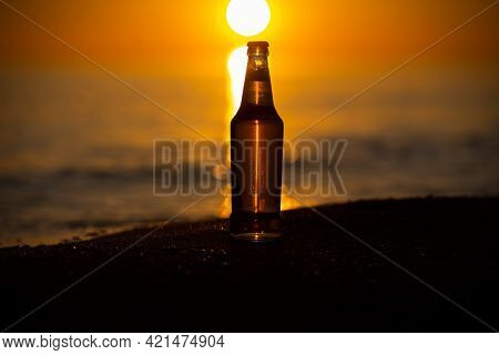 An Ice Cold Beer / Soda Bottle Standing Straight On The Golden Sands At Sunset. Summer Evening