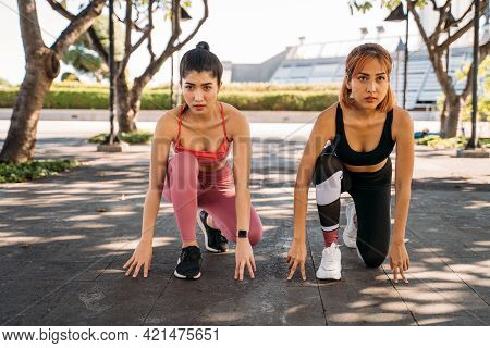 Young Asian Female Friends In Sportswear Sitting In Starting Position Prepared To Compete And Run Ag