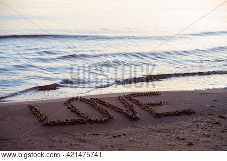 Love Sign Whiten On The Sand At The Beach. Romantic Love Symbol At Tropical Seashore At Sunset.