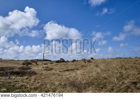 Dune Valley With Beach Grass And A Blue Sky And In The Background A Classic, Historic Old Red And Wh