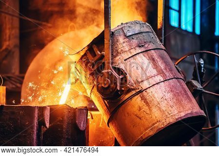Molten Metal Pour From Ladle Into Sand Mold. Iron Casting Process In Metallurgy Foundry Plant, Heavy