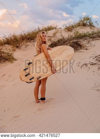 Surfer Girl With Surfboard On Beach And Warm Sunset Colors. Attractive Surfer Women