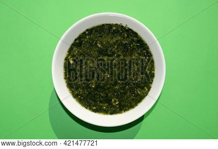 Famous Traditional Arabic Cuisine. Molokhia Soup In A White Bowl On A Green Background. Flat Lay, To