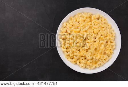 Macaroni And Cheese On A White Plate On A Black Background. American Mac And Cheese