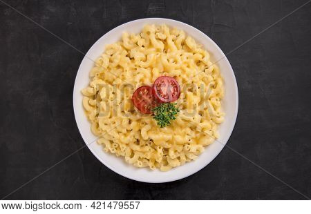 Macaroni And Cheese On A White Plate With Parsley And Cherry Tomatoes On A Black Background. America