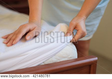 Woman's Hand Puts A Cover On The Mattress To Protect It From Water And House Dust Mites