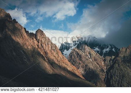 Scenic Landscape With Great Rocks And Snowy Mountains In Sunlight In Low Clouds. Wonderful View To M