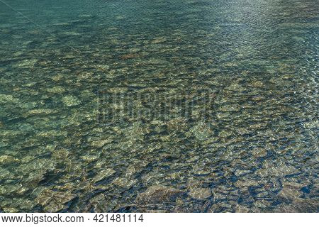 Beautiful Nature Background Of Stony Bottom In Turquoise Transparent Water Of Glacial Lake In Sunlig