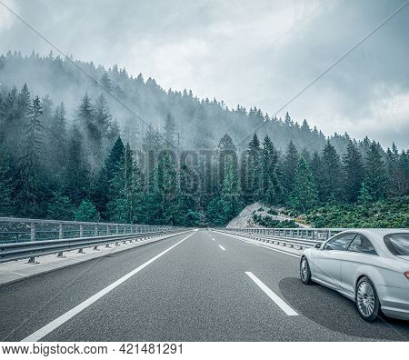 A White Car Drives Down The Road Through The Forest Along The Highway.
