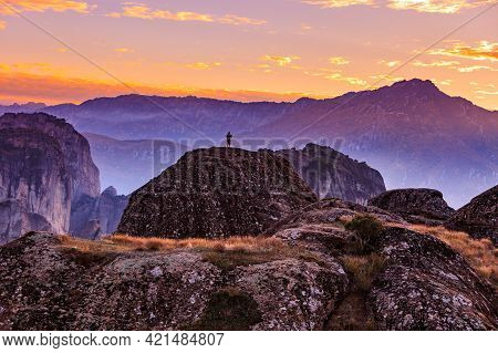 Tourist In Mountains At Sunset, Person On Cliffs Rocky Formations In Thessaly Greece. Tourism Vacati