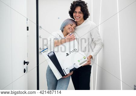 Happy Young Couple Just Came Home From Store With A Brand New Sony Playstation 5 Gaming Console. The
