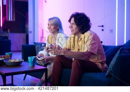 Photo Of Young Couple Playing Video Games At Home At Night