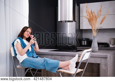 Young Beautiful Woman Using Cell Phone While Sitting In The Kitchen After Coming Back Home From Work