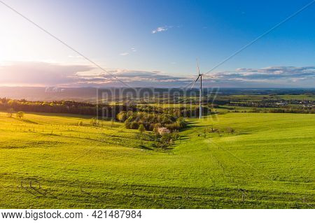 Wind Turbine In Green Rural Landscape In Contrast To Coal Power Plant On Background . Aerial View Fr