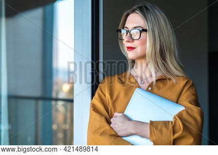 Business woman, teacher with laptop standing on terrace, fresh air, work, study from home. Long distance communication. Staying connected