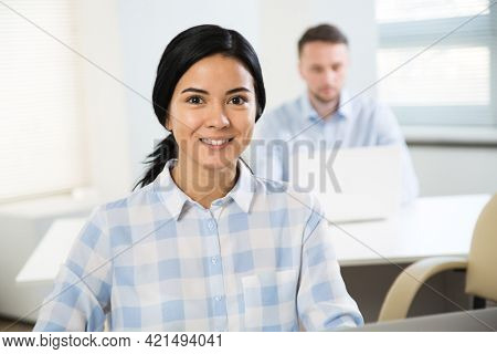 Portrait of young businesswoman and her colleague on the background at the office