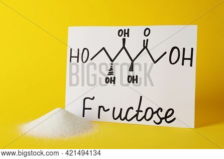 Pile Of Sugar And Word Fructose With Drawn Scheme On Paper Against Yellow Background