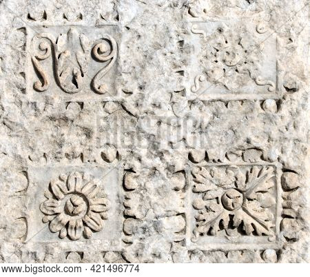 Square background with ancient carved ornament with flower on a stone wall. Ancient roman bas-relief with floral ornament