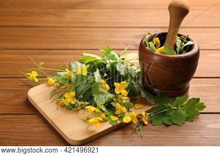 Celandine With Board, Mortar And Pestle On Wooden Table