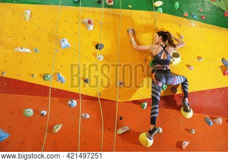 Athletic Woman Climbing Wall In Gym. Space For Text