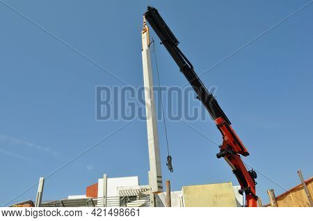 Crane Lowering Concrete Beam In Urban Construction In Brazil, South America With Bottom-up View To T
