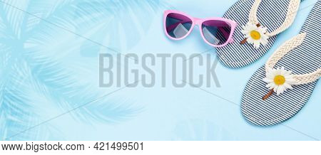 Beach flip flops with flowers and sunglasses on blue background. Summer vacation concept. Flat lay with copy space