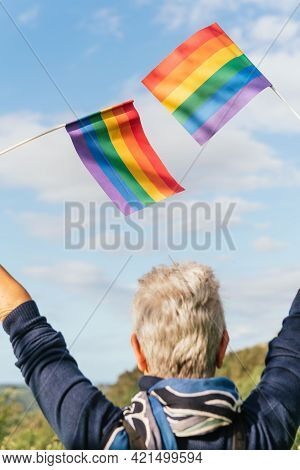 Older Woman With White Hair Waving Two Rainbow Gay Pride Flags. Senior Person Of The Lgbt Collective